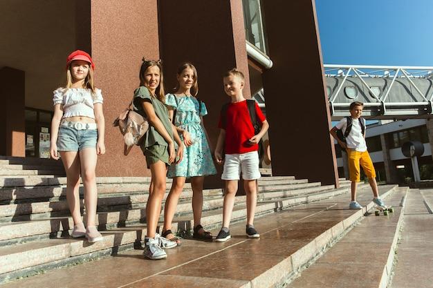 Gelukkige kinderen spelen op straat van de stad in zonnige zomerdag voor modern gebouw. groep gelukkige kinderen of tieners die samen plezier hebben. concept van vriendschap, jeugd, zomer, vakantie.