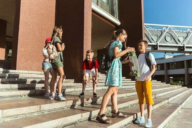 Gelukkige kinderen spelen op straat van de stad in zonnige zomerdag voor modern gebouw. groep gelukkige kinderen of tieners die samen plezier hebben