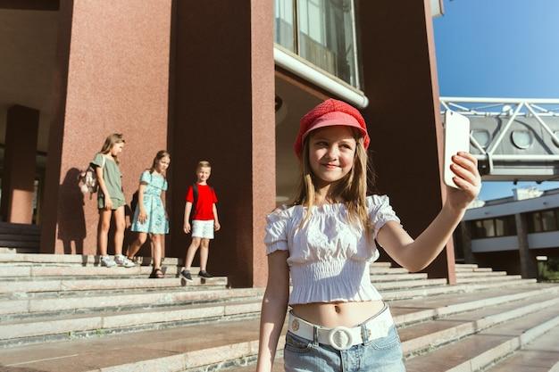 Gelukkige kinderen spelen op straat van de stad in zonnige zomerdag voor modern gebouw