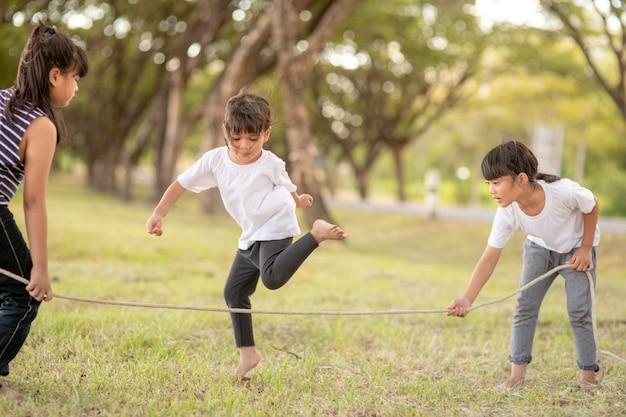 Gelukkige kinderen spelen samen met touwtjespringen buiten