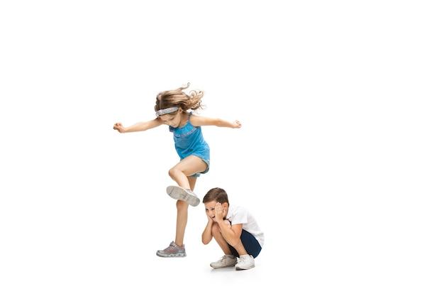 Gelukkige kinderen springen en plezier geïsoleerd op een witte muur