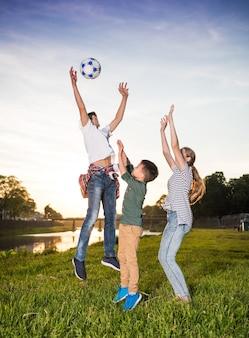 Gelukkige kinderen springen en spelen met de bal buitenshuis. zonnige zomerdag