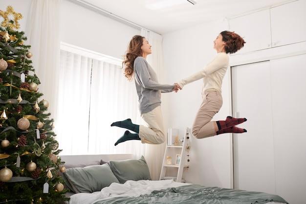 Gelukkige kinderen springen, plezier maken, spelen op bed in de slaapkamer genieten van de ochtend