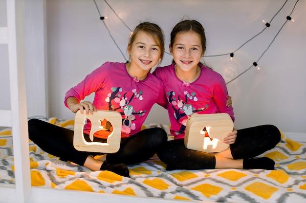 Gelukkige kinderen, twee lachende schattige zusjes van 10-jarige meisjes, in de kinderkamer op een stapelbed, zittend in lotushouding en met houten nachtlampjes met uitgesneden afbeeldingen.