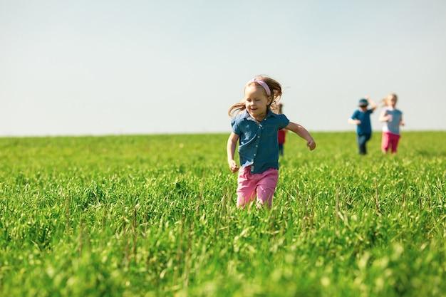 Gelukkige kinderen van jongens en meisjes rennen in het park op het gras op een zonnige zomerdag