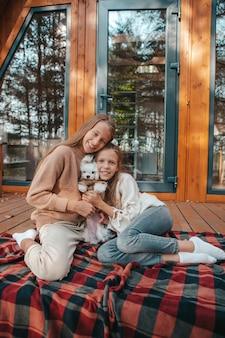 Gelukkige kinderen zitten in de herfst op het terras van hun huis