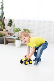Gelukkige kinderjaren - kleine vrolijke kleine jongen die thuis met stuk speelgoed auto speelt