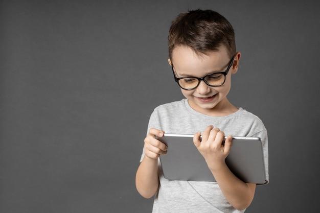 Gelukkige kindjongen die een tabletipade voor uw informatie over de blauwe achtergrond houdt