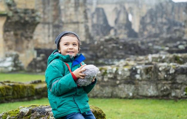 Gelukkige kindjongen die warme doeken draagt die zijn zacht stuk speelgoed, zittend op oude bakstenen muur met wazige ruïnes van oude abdijachtergrond houden