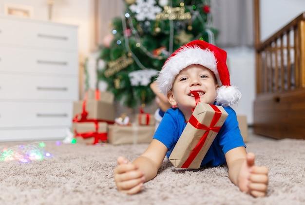 Gelukkige kindjongen ontvangt op kerstochtend een cadeautje dat op een gezellig tapijt in zijn kamer in pyjama ligt