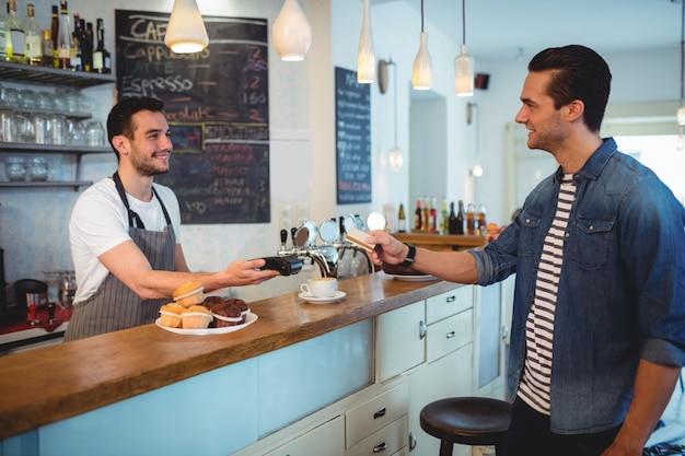 Gelukkige klant die creditcard geven aan barista bij koffiewinkel