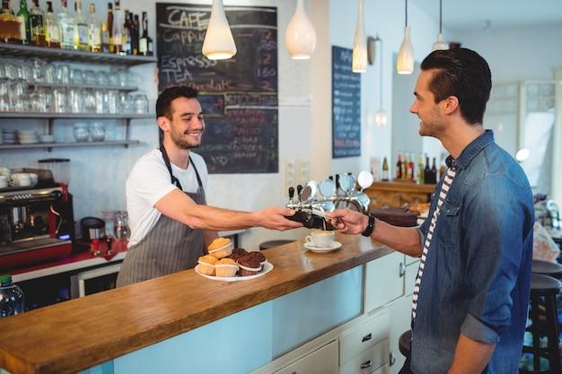 Gelukkige klant die door creditcard bij koffiewinkel betaalt