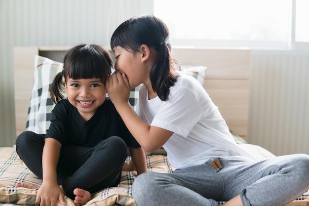 Gelukkige kleine aziatische broers en zussen die geheimen delen