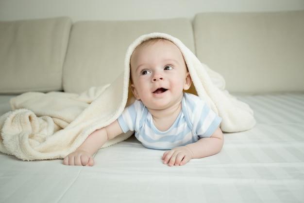 Gelukkige kleine baby die op bed onder deken kruipt