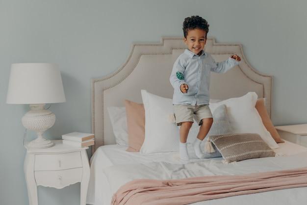 Gelukkige kleine energieke afro-amerikaanse jongen die alleen op het bed van zijn ouders springt terwijl hij heerlijke lolly vasthoudt, snoep eet, rotzooi veroorzaakt terwijl niemand thuis is, schattig kind dat thuis plezier heeft