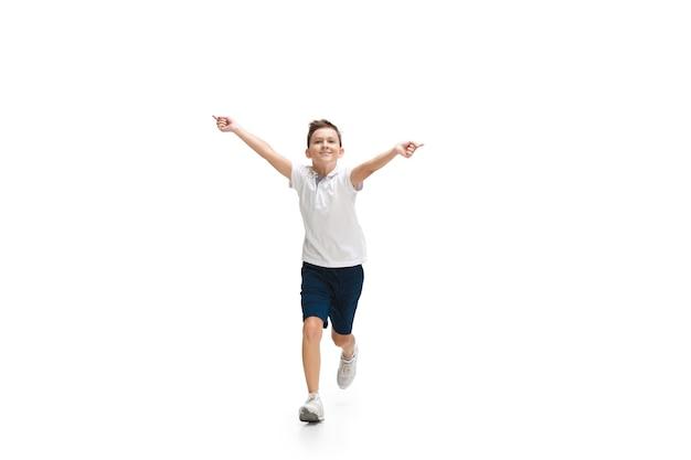 Gelukkige kleine jongen die op witte muur loopt
