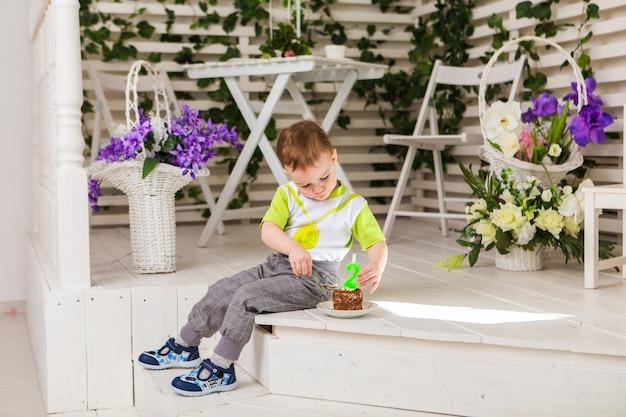 Gelukkige kleine jongen die zijn verjaardag viert, houdt een fluitje van een cent, binnen. verjaardagsfeestje voor kinderen. zorgeloze jeugd, geluk. twee jaar oud.