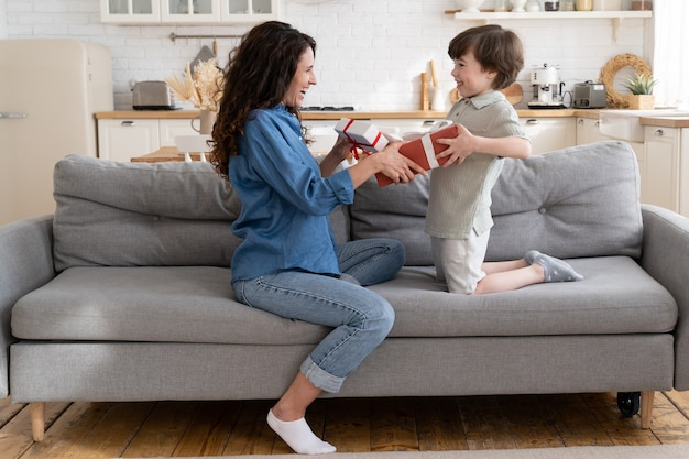 Gelukkige kleine jongen en jonge moeder geven elkaar geschenkdozen die moeder en kind begroeten met verjaardag
