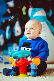 Gelukkige kleine jongen in de buurt van speelgoed sneeuwpop in de studio