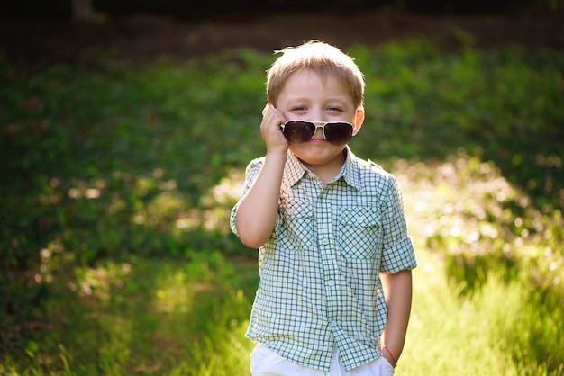 Gelukkige kleine jongen met zonnebril in de tuin.