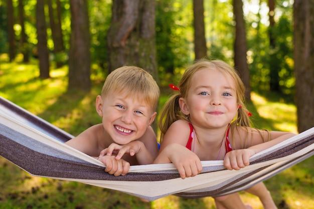 Gelukkige kleine kinderen, broer en zus liggen in de zomer in een hangmat
