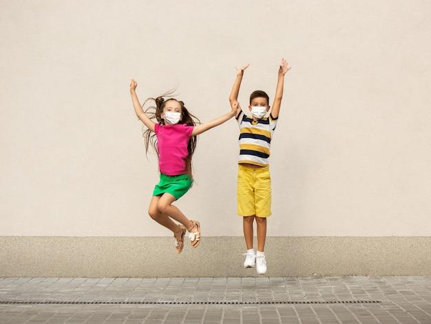 Gelukkige kleine kinderen die een beschermend gezichtsmasker dragen, springen en rennen op straat in de stad. ziet er gelukkig, vrolijk, oprecht uit. kopieerruimte. jeugd, pandemisch concept. gezondheidszorg, coronavirus pandemie.