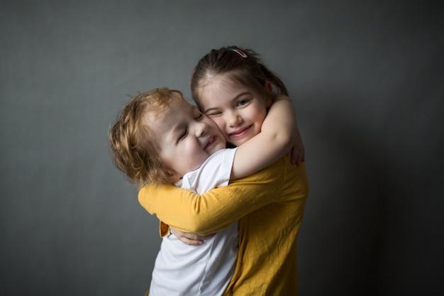 Gelukkige kleine kinderen die elkaar knuffelen