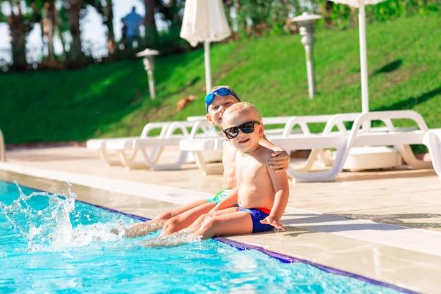 Gelukkige kleine kinderen die plezier hebben aan het zwembad in het vakantieoord