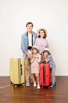 Gelukkige kleine kinderen en hun moeder in hoeden die naast de jonge man staan terwijl ze een gezinsreis gaan hebben