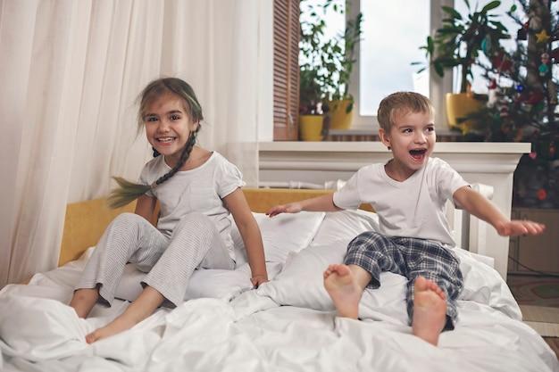 Gelukkige kleine kinderen in pyjama's springen in bed in de slaapkamer