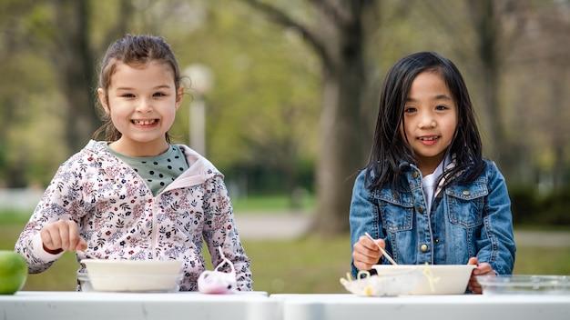 Gelukkige kleine kinderen lunchen buiten in het stadspark, leren groepsonderwijs concept.