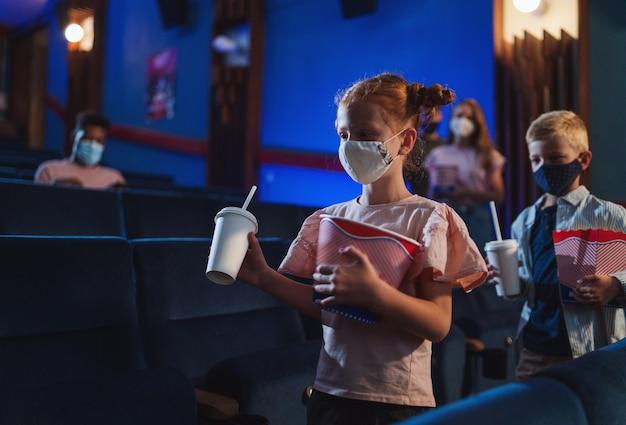 Gelukkige kleine kinderen met popcorn wandelen in de bioscoop een coronavirusconcept