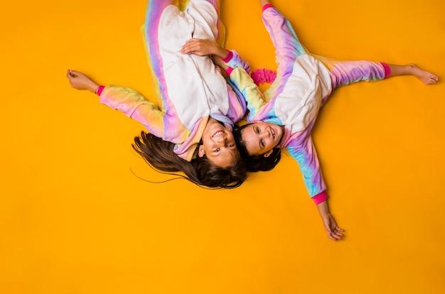 Gelukkige kleine meisjes in pluche pyjama's liggen op een gele achtergrond met een kopie van de ruimte