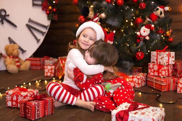 Gelukkige kleine meisjes in rode pyjama's versieren een kerstboom in de woonkamer