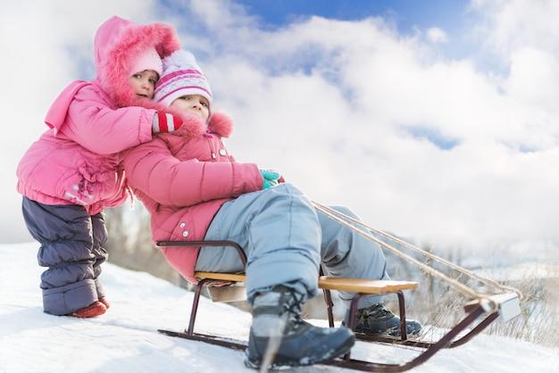 Gelukkige kleine meisjes in roze de winterkleding die bergaf in sneeuw sledding