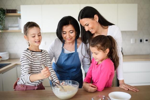 Gelukkige kleine meisjes met moeder en een grootmoeder die thuis pannenkoekenmengsel maken, koken.