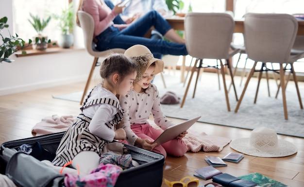 Gelukkige kleine meisjes met tablet binnenshuis thuis, inpakken voor zomervakantie.