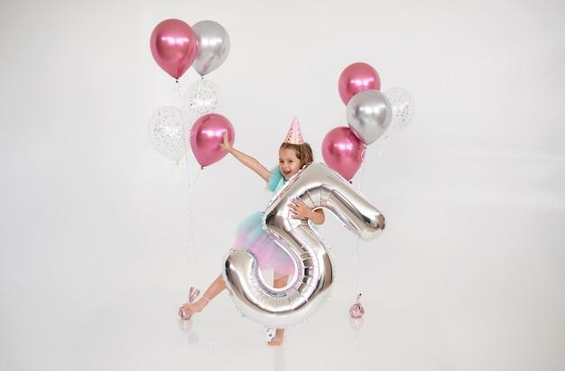 Gelukkige kleine verjaardag meisje dansen met ballonnen en folie nummer vijf op een witte achtergrond