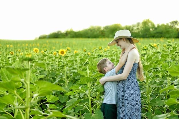 Gelukkige kleine zoon omhelst zwangere moeder die op een veld met bloeiende zonnebloemen staat