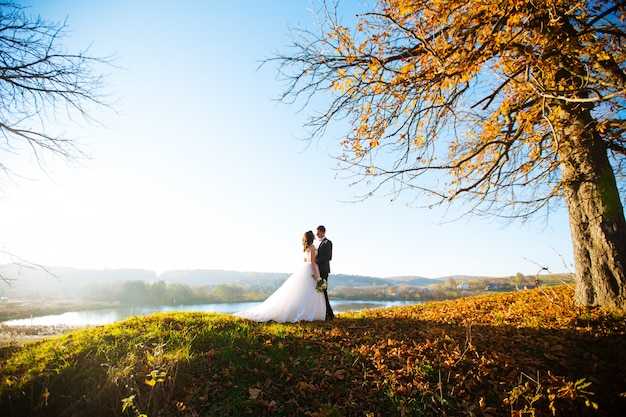 Gelukkige knappe bruidegom en beautifylbruid die op balkon bij zonsondergangclose-up koesteren
