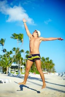 Gelukkige knappe gespierde man in sunhat op strand springen achter blauwe hemel achter blauwe hemel