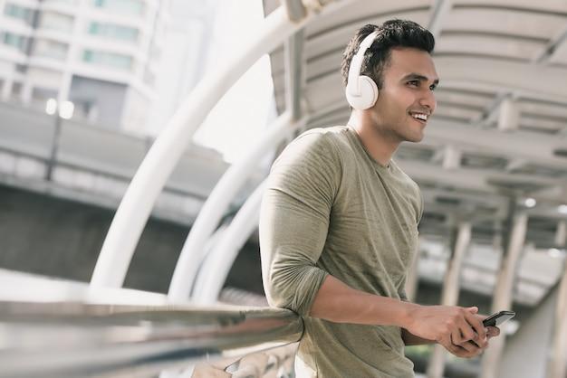 Gelukkige knappe indische mens die hoofdtelefoons draagt die aan muziek luisteren