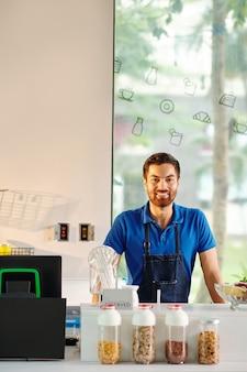 Gelukkige knappe jonge man aan het werk in het ontbijtcafé dat hij net heeft geopend