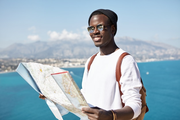 Gelukkige knappe jonge mannelijke reiziger met een donkere huid die op de top van een berg staat met een papieren kaart boven de uitgestrekte oceaan en de badplaats, met een vreugdevolle blik terwijl hij de wereld rondreist in gezelschap van vrienden