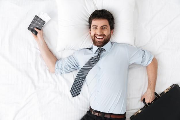 Gelukkige knappe jonge zakenman in de ochtend in bed ligt met paspoort