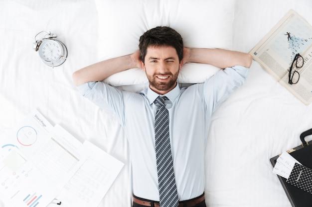 Gelukkige knappe jonge zakenman in de ochtend in bed ligt
