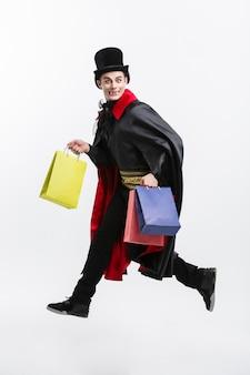 Gelukkige knappe kaukasische vampier die kleurrijke het winkelen zak op witte achtergrond houdt.