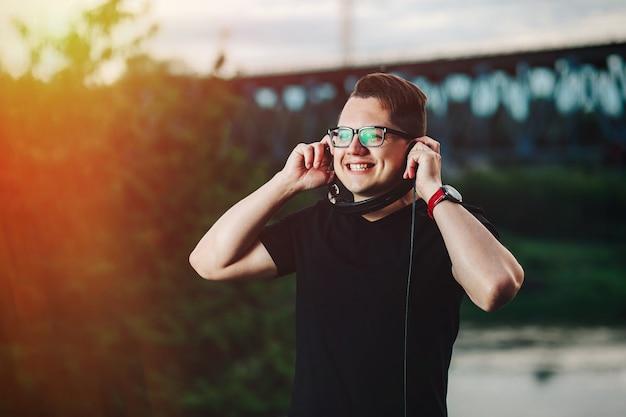 Gelukkige knappe kerel die aan muziek in zonlicht luistert