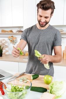 Gelukkige knappe kerel kokende salade met laptop
