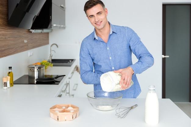 Gelukkige knappe man in blauwe stront die staat en kookt in de keuken